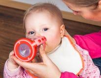Mother feeding infant girl Stock Images