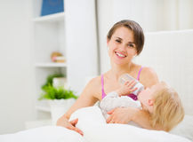 Mother feeding kid in bed Royalty Free Stock Photography
