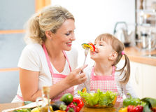 Mother feeding kid daughter vegetables Royalty Free Stock Image