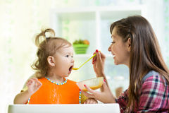 Mother feeding kid with spoon indoors Royalty Free Stock Photo
