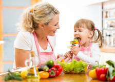 Mother feeding kid vegetables in kitchen Stock Photos