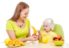 Mother feeding little girl with healthy food sitting at table Stock Images