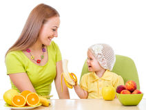 Mother feeding little girl with healthy food sitting at table. Isolated on white royalty free stock image