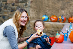 Mother feeding little kid girl with hot dog outdoors Royalty Free Stock Photo