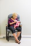 Mother Feeding Milk To Newborn Baby Girl On Chair stock photography
