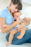 Mother feeding 3 months old baby from bottle. Mother feeding her 3 months old baby from bottle Royalty Free Stock Image