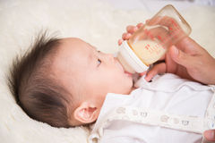 Mother feeding mother breast feeding milk from bottle baby infant 7 months Stock Photography