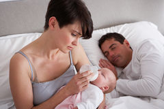 Mother Feeding Newborn Baby In Bed Stock Photos