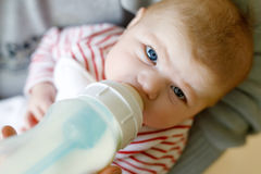 Mother feeding newborn baby daughter with milk in nursing bottle. Formula drink for babies. New born child, little girl laying in bed. Family, new life royalty free stock photos
