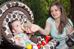 Mother feeding newborn son with feeding bottle Royalty Free Stock Photo