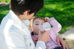 Mother feeding one year baby girl with feeding bottle Stock Photography