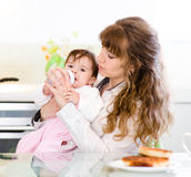Mother feeding sad baby with feeding bottle Royalty Free Stock Photography