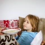 Mother feeding taken ill daughter by semolina. Spoonfeeding Stock Photography