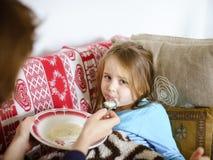 Mother feeding taken ill daughter by semolina. Spoonfeeding Stock Photos