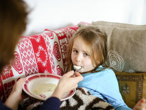 Mother feeding taken ill daughter by semolina Stock Images