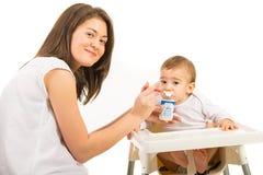 Mother feeding toddler boy. Mother feeding her toddler boy with yogurt isolated on white background Royalty Free Stock Photos