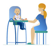 Mother feeding a young child in highchair. With a spoon Stock Photography