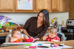 Mother Feeds Babies. A mother in the kitchen feeds babies breakfast royalty free stock photos