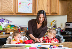 Mother Feeds Babies. A mother in the kitchen feeds babies breakfast royalty free stock image