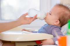 Mother feeds baby from a bottle of milk Stock Images