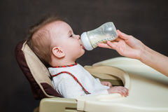 Mother feeds baby from a bottle of milk Royalty Free Stock Photo