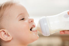 Mother feeds baby from a bottle of milk Stock Photography