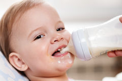 Mother feeds baby from a bottle of milk Royalty Free Stock Photography