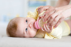 Mother feeds the baby bottle in nursery. Mother feeds infant baby bottle in nursery Royalty Free Stock Photo