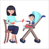 Mother Feeds Baby Boy who sits on Toddler Carriage Royalty Free Stock Photos