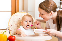 Mother feeds baby stock photography