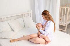 Mother feeds baby 6 months of breast sitting on a white bed at home, place for text