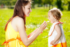 Mother feeds baby outdoors in the grass Royalty Free Stock Images
