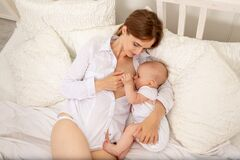 The mother feeds the baby`s chest on the bed, the concept of family baby food