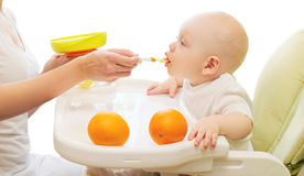 Mother feeds baby spoon on table home Stock Photography