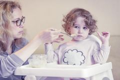 The two-year-old child is naughty and refuses to eat. Mother feeds the baby with a spoon. The two-year-old child is naughty and refuses to eat Royalty Free Stock Photos