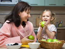 Mother feeds the child with apples stock photos