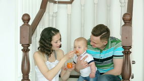 The mother feeds the child, and dad is holding him. Happy family. Mom dad and 6 month old baby. Family sitting on the stairs at ho stock video