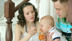 The mother feeds the child, and dad is holding him. Happy family. Mom dad and 6 month old baby. Family sitting on the stairs at ho stock footage
