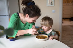 Mother feeds the child soup in the bright kitchen at home Stock Image