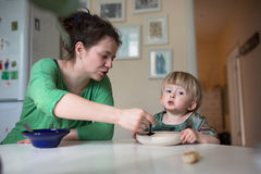 Mother feeds the child soup in the bright kitchen at home Stock Images