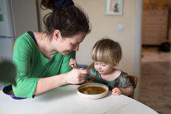 Mother feeds the child soup in the bright kitchen at home Stock Photos