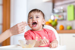 Mother feeds funny baby from a spoon Royalty Free Stock Photos