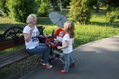 Mother feeds her baby with a spoon in a summer's day and sister concerns Royalty Free Stock Photography