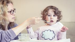 Mother feeds her cute baby with a spoon stock images
