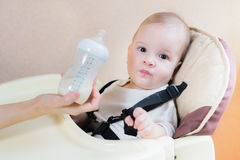 Mother feeds her nine-month baby milk house Royalty Free Stock Photos