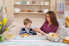 Mother feeds her son, happy family breakfast. Mother and son having breakfast. Happy mother and son in the kitchen. Concept of happy family and healthy food Stock Photo