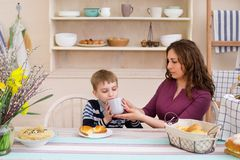 Mother feeds her son. Mother and son having breakfast. Happy mother and son in the kitchen. Concept of happy family and healthy food Stock Photography