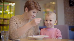 Mother feeds her son with a spoon stock video footage
