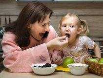 Mother feeds little child Stock Images