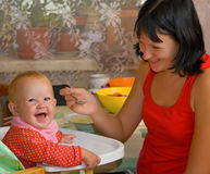 Mother feeds the little daughter. Mother feeds the little smiling daughter from a spoon Stock Photo